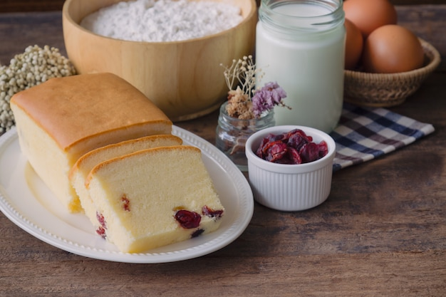 Slices of homemade butter cake with dried cranberries on white plate