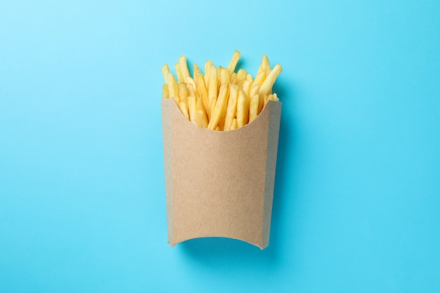 Slices of hot french fries in box on blue. top view