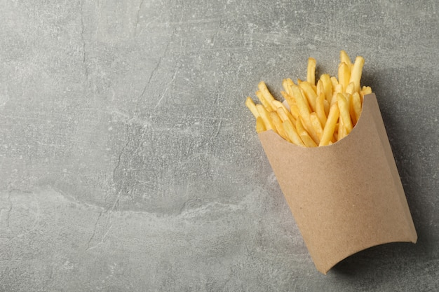 Slices of hot french fries in box on grey. top view