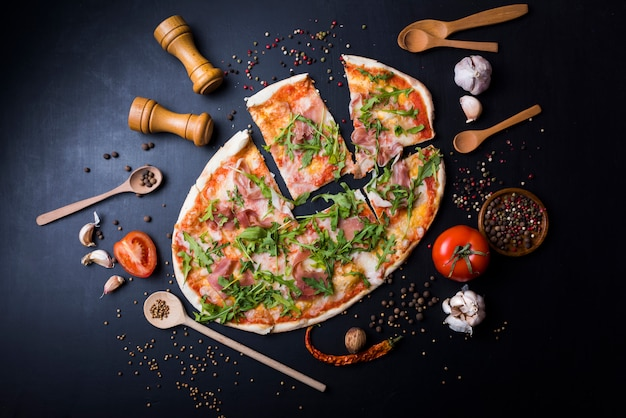 Slices italian pizza with utensils and ingredients over black kitchen worktop