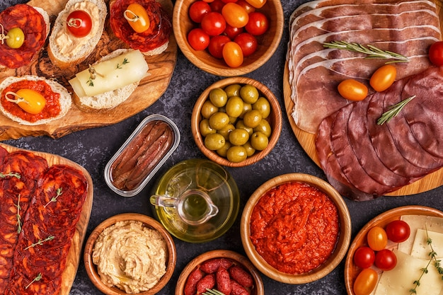 Slices jamon, chorizo, sausage, bowls with olives, tomatoes, anchovies,  mashed chickpeas, cheese.