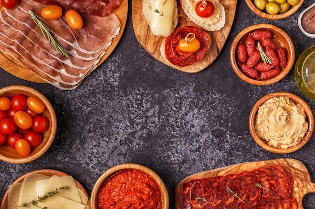 Ломтики хамона, чоризо, колбасы, тарелки с оливками, помидорами, анчоусами, пюре из нута, сыром.