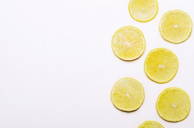 Slices of juicy yellow lemon on white background