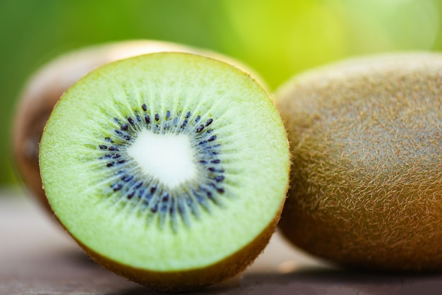 Slices kiwi close up and fresh whole kiwi fruit on wooden and nature green background