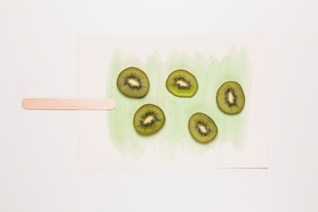 Slices kiwi fruit on watercolor painted in shape of ice cream