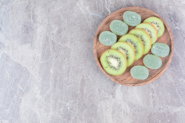 Slices of kiwi and marmalades on wooden plate.
