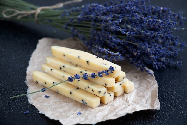 Slices of lavender cheese with sprigs of lavender on parchment paper with a dark background