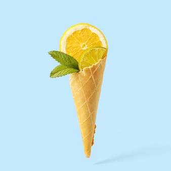 Slices of lemon, lime and mint in a waffle horn stylized as ice cream. creative concept.