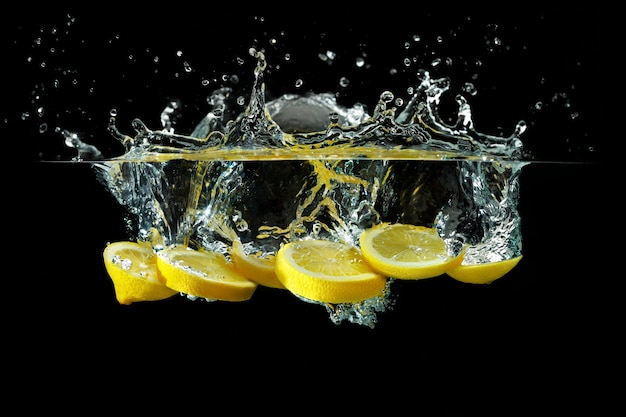 Slices of lemon thrown into water on a black background