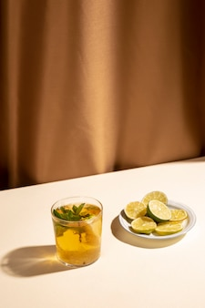 Slices of lemon with cocktail drink over white desk