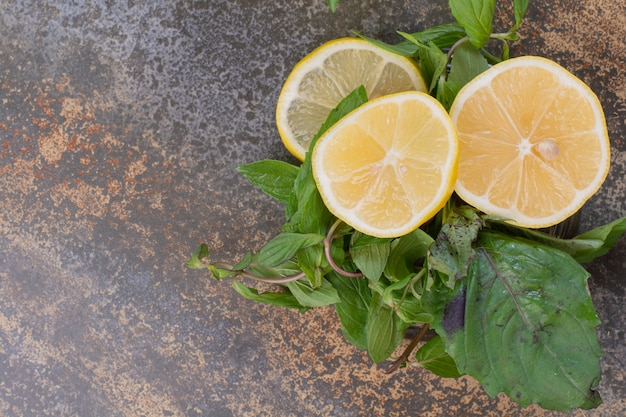 Slices of lemon with mint on marble surface