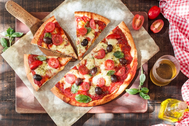 Slices of margherita pizza on chopping board with ingredients