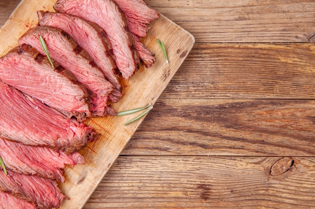 Slices of medium rare roast beef meat on wooden cutting board. copyspace.