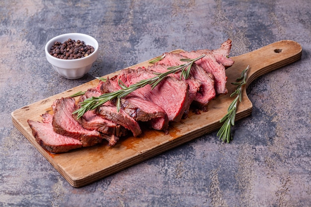 Slices of medium rare roast beef meat on wooden cutting board