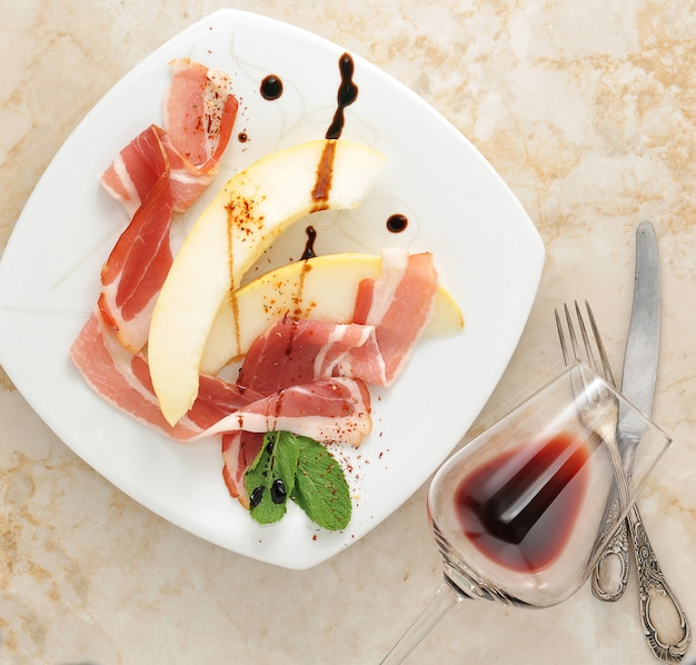 Slices of melon wrapped in bacon with mint leaves and strawberry and glass of red wine