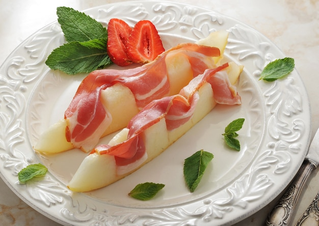 Slices of melon wrapped in bacon with mint leaves and strawberry on marble