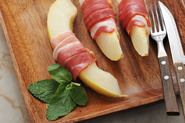 Slices of melon wrapped in bacon with mint leaves on wooden platter