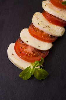 Slices of mozzarella cheese and tomatoes with pepper seasoning and herbs on black background