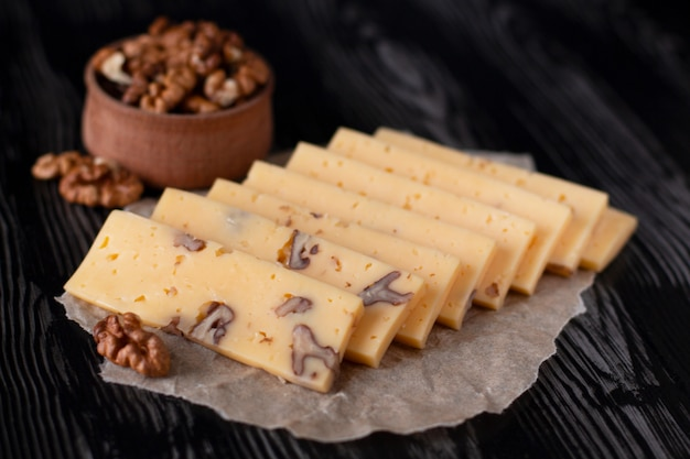 Slices of nut cheese with nuts on parchment paper with a dark background