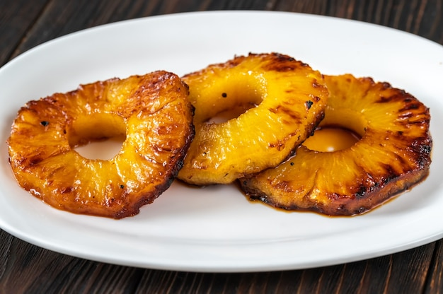 Ломтики жареного карамелизованного ананаса на сервировочной тарелке