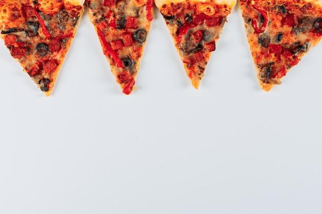 明るい漆喰背景に平らなピザのスライスを置く