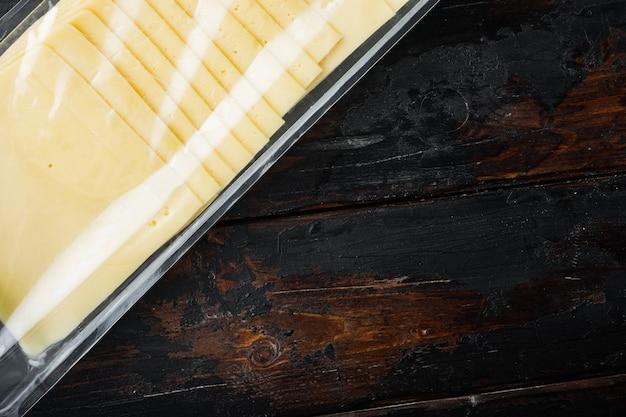 텍스트 복사 공간이 어두운 나무 배경에 플라스틱 팩에 아메리칸 치즈 조각
