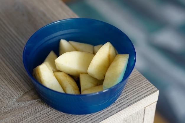 テーブルの上の青いボウルにリンゴのスライス