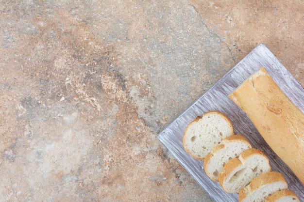 나무 보드에 바게트 빵 조각