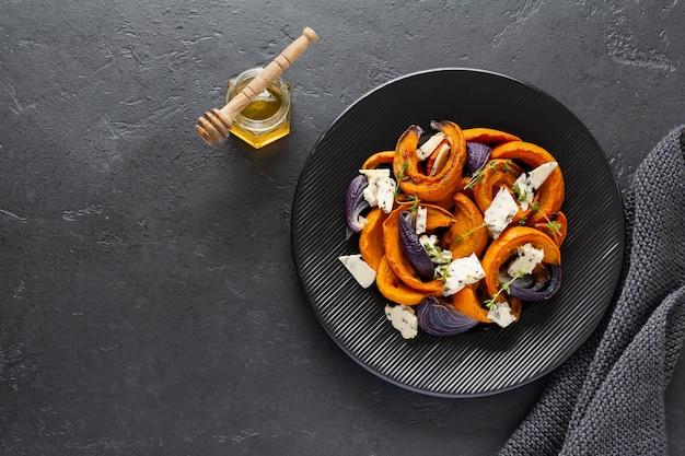 Ломтики запеченной тыквы, лука, чеснока, специй и ломтики сыра дорблю на черной керамической тарелке и старом черном камне