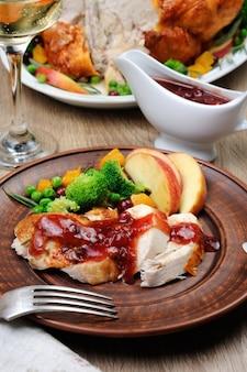 焼き七面鳥のスライスとクランベリーオレンジソースと果物と野菜を飾る