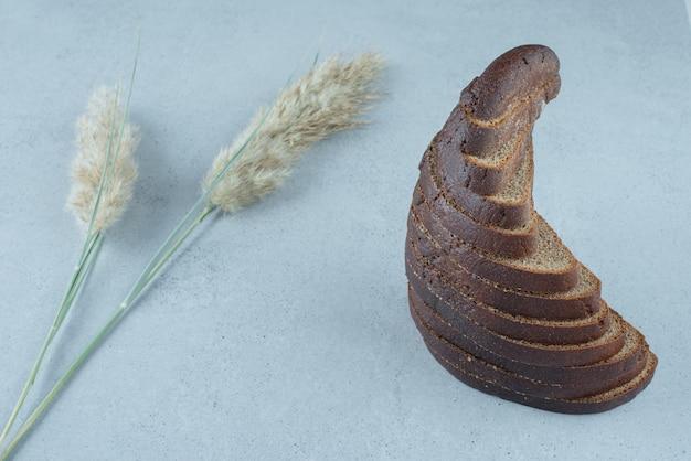 Ломтики черного хлеба на каменной поверхности с пшеницей