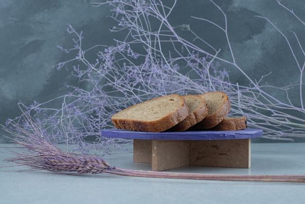 Ломтики черного хлеба на деревянной доске с пшеницей