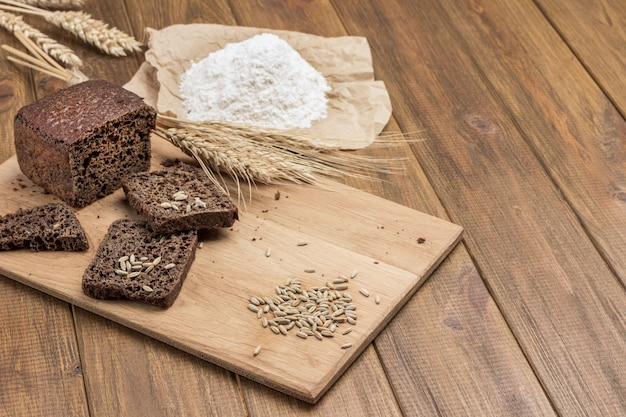 パンのスライスとパンの塊、まな板の上のライ麦とライ麦の小穂。テーブルの上の紙に小麦粉。上面図