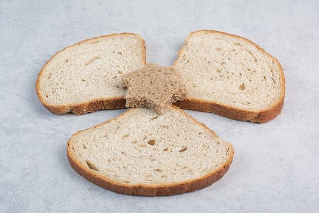 Ломтики хлеба и хлеба в форме звезды на мраморном фоне. фото высокого качества