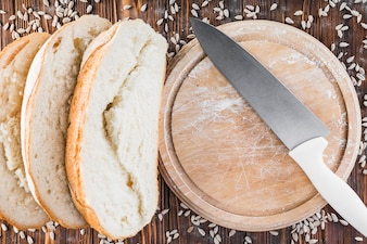 Slices of bread and sunflower seeds on wooden chopping board with knife