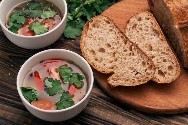 Ломтики хлеба и две тарелки супа на кухонном столе