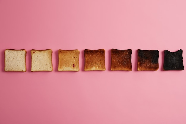 トーストのさまざまな段階でのパンのスライス。ピンクの背景の上に一列に配置されたカリカリのトーストスライス。最後の1つは完全に焼けました。トーストを作る。未焙煎から焦げ目まで。トップダウンビュー