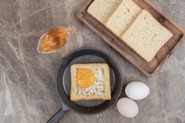 Кусочки хлеба, яиц и масла на мраморном столе. фото высокого качества