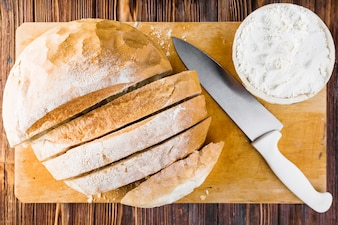 Slices of bread, knife and bowl of flour on chopping board