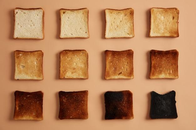 ベージュの背景に並べられたさまざまな程度のトーストのパンのスライス。トーストやおやつを食べましょう。乾杯の段階。健康的な食事、マンチ、ダイエットのコンセプト。スタジオ写真