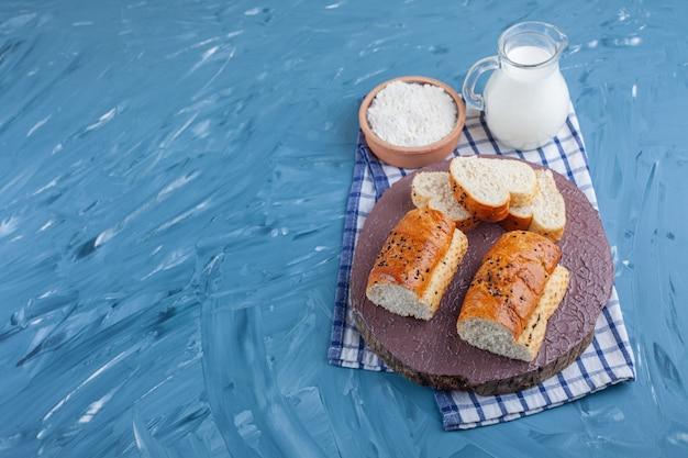 삶은 계란 옆 보드에 빵 조각과 파란색 테이블에 수건에 밀가루 한 그릇.