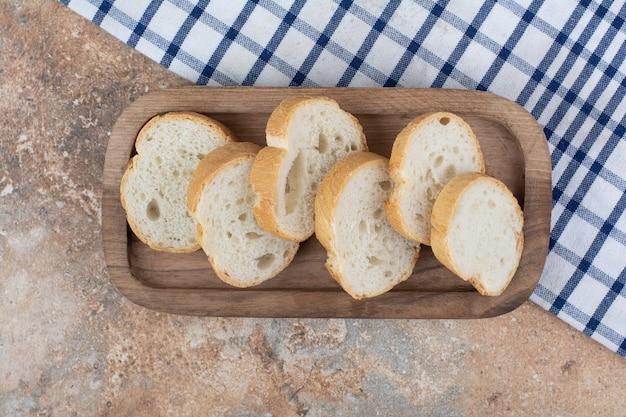 식탁보와 나무 접시에 빵 조각