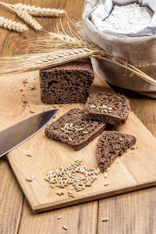 まな板の上にパン、ライ麦、ナイフのスライス。一斤のパンにライ麦の小穂。テーブルの上のバッグに小麦粉。上面図