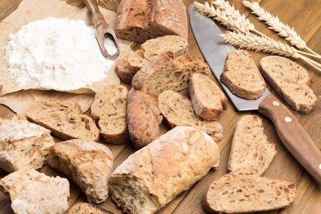 パン、ライ麦、ナイフのスライス。テーブルの上の紙に小麦粉
