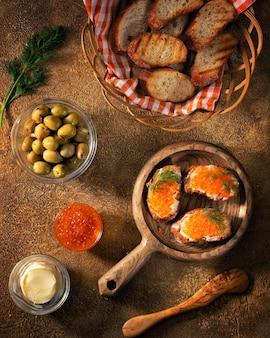 올리브와 버터와 함께 테이블에 배치 빨간 캐 비어와 함께 빵 조각 확산. 베이커리 음식 개념 또는 배너 사진입니다.