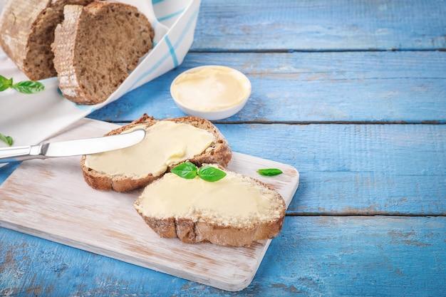 青い木製のまな板にバターとパンのスライス