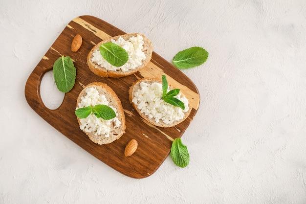 白い背景の上の木製のまな板にカッテージチーズとミントの葉とパンのスライス。上面図。スペースをコピーします。