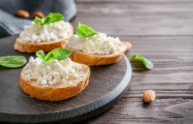 木製の背景の木製まな板にカッテージチーズとミントの葉とパンのスライス。