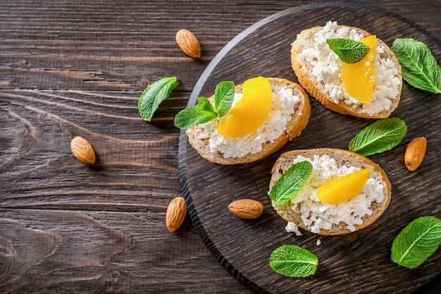 木製の背景の木製まな板にカッテージチーズ、ミントの葉、桃の部分とアーモンドナッツとパンのスライス。上面図。