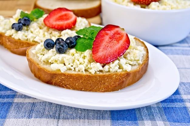 カードクリーム、ミント、ブルーベリー、イチゴ、カッテージチーズのボウル、青い市松模様のテーブルクロスの背景にボード上のパンのスライス